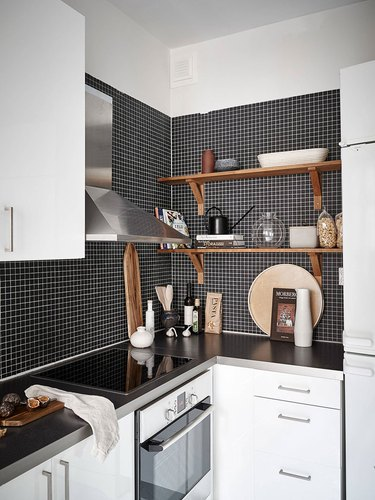 black and white kitchen with black mosaic tiles