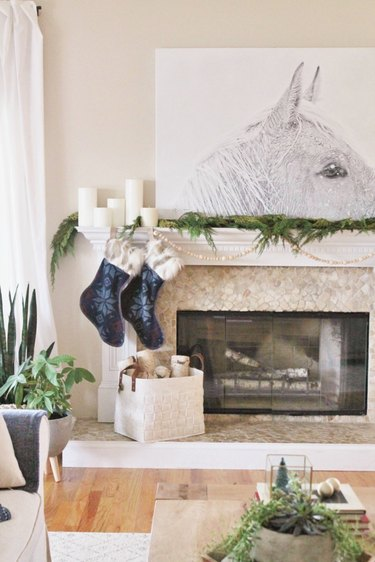 Neutral walls and fireplace with dark blue stockings