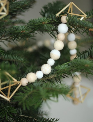 Himmeli geometric ornaments strung with wooden beads on a tree