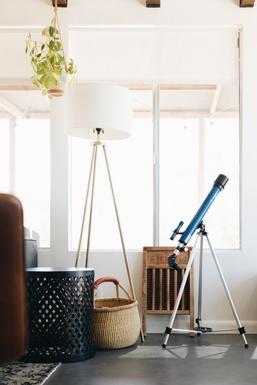 telescope in cabin living room near window and floor lamp
