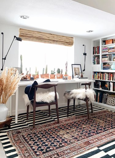 Home Office for Two Shared desk with layer area rugs, sheepskin on chairs, bamboo blind, cacti, bookshelves.