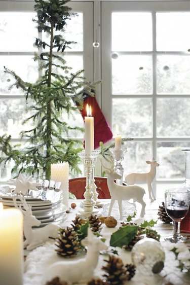 A white tablescape with evergreen accents