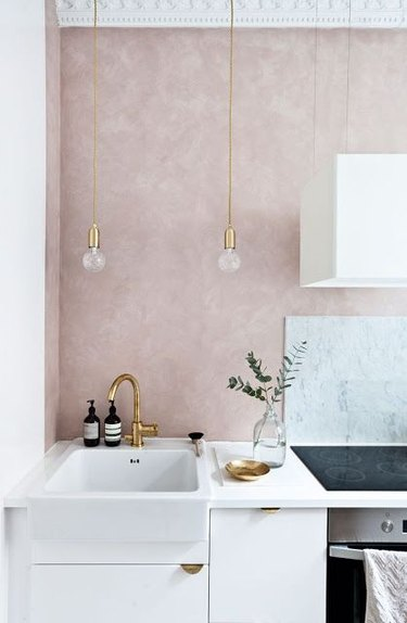 minimal pink kitchen accent wall with marble backsplash and white cabinets