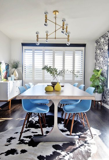 Midcentury dining room idea with blue chairs and patterned wallpaper