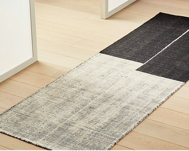 wood floor with handloomed gray and white runner