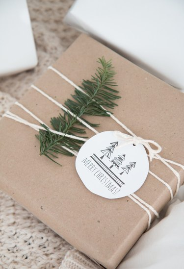 Brown wrapped gift with a fir leaf and white minimal gift tag