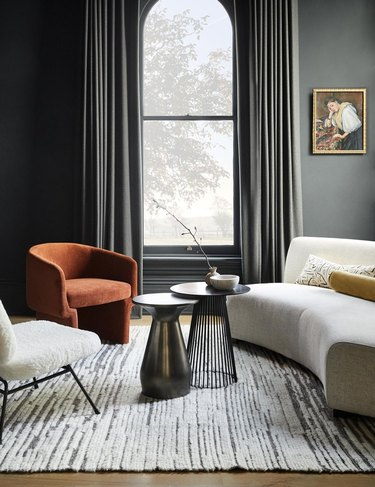 gray room with white sofa and terra cotta color arm chair