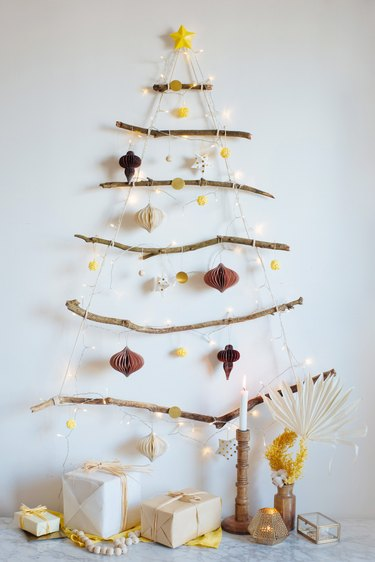 branch and twinkly light DIY Christmas tree hung on the wall