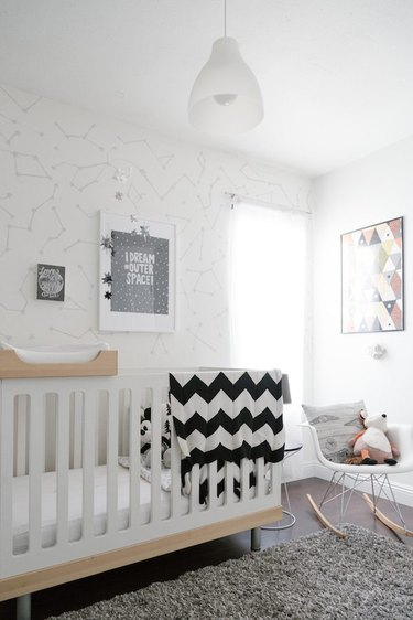 a white celestial-theme nursery with modern rocking chair