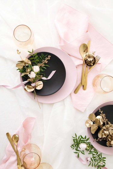 Pink plates and napkins with gold and black accents