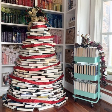 stacked-book DIY Christmas tree with red ribbon in library