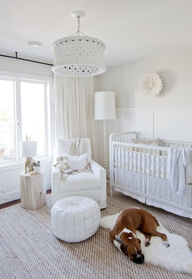 a neutral white nursery with upholstered rocker and sheepskin rug