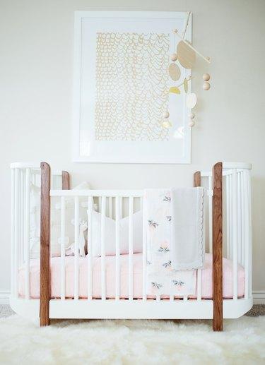 a white boho nursery with crib and decorative mobile
