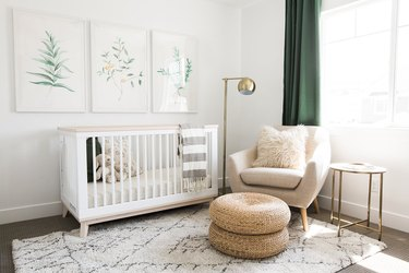 a white nursery with green drapery and nature-inspired artwork