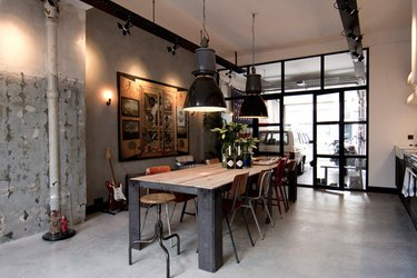industrial dining room idea with concrete walls and flooring and steel table with wood top and factory style pendant lights