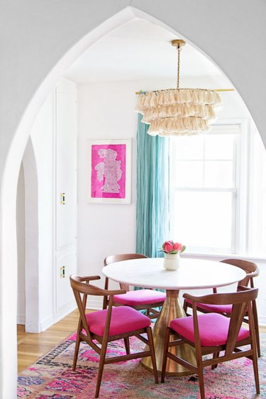fuchsia pink dining room with aqua curtains and a tassel chandelier
