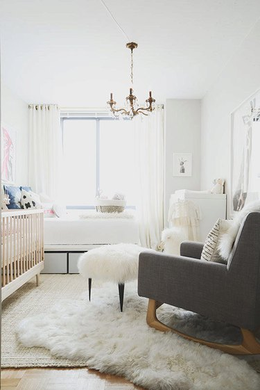 white nursery with gold candelabra chandelier and sheepskin rug
