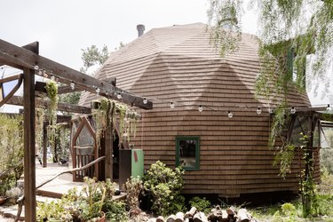 A brown dome-shaped home with a lush garden and string lights strung off the pergola