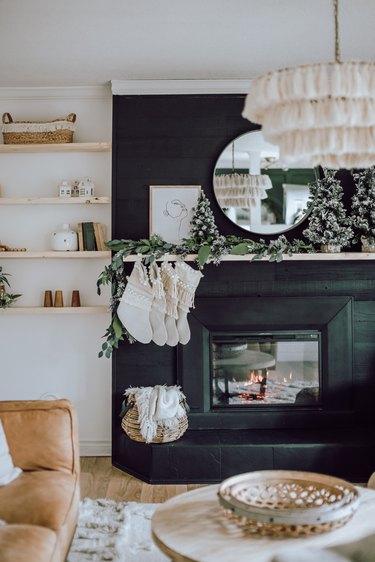 Black fireplace with macrame stockings, boho decor, and tasseled chandelier