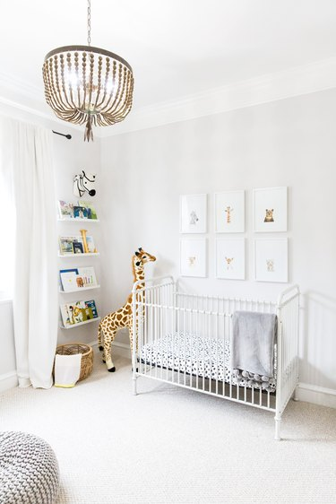 white nursery with framed prints of baby animals and beaded chandelier