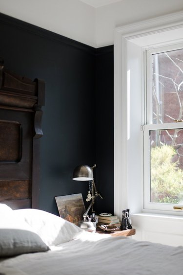 townhouse with black bedroom wall and carved wood headboard