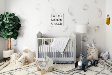 moon wallpaper mural in a white nursery with gray crib