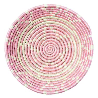 Pink and white woven decorative bowl with star design in the middle