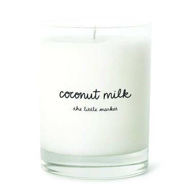 """White candle with text """"Coconut milk"""" in cursive"""