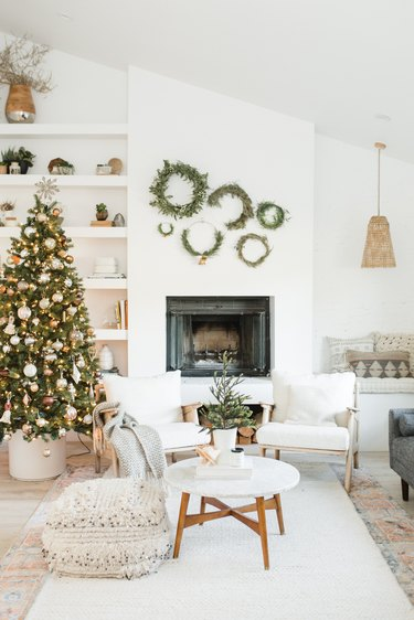 white christmas tree decorations in living room with fireplace and multiple wreaths