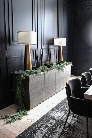 Black dining room with black accent wall, tapered candles, brass lamps, and ornaments in greenery