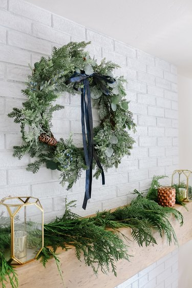 Winter wreath with navy blue bow above Christmas mantel