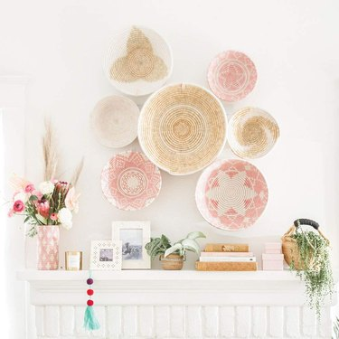 Seven decorative woven bowls featuring white, beige, and light pink hues on wall