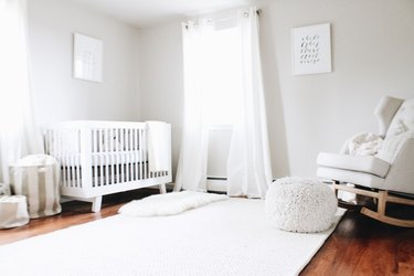 minimal white nursery with upholstered rocker and pouf