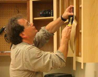 Man refacing cabinets.