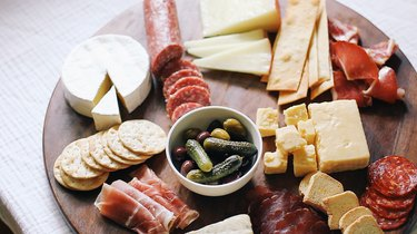 Bowl of olives and cornichons added to board