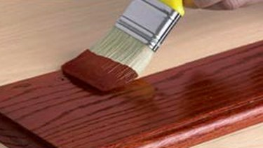 Staining wood with a brush.