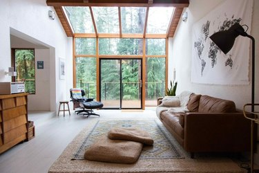 Living room space with large windows, couch and chair