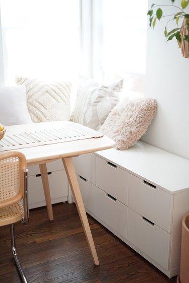 Modern white dining room storage idea with under-the-seat storage