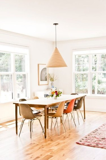 dining room curtain idea with roller shades in white midcentury space with mismatched chairs