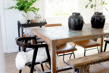 dining room idea with rustic table and mismatched chairs and bar cart near table