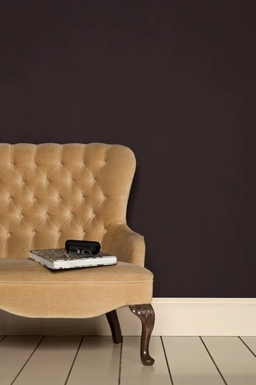 yellow armchair in front of brown wall