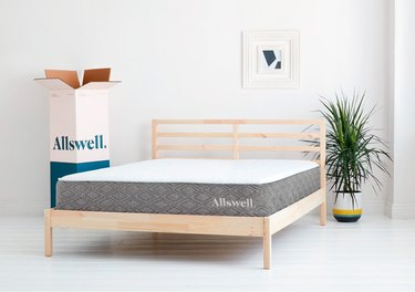 white and gray mattress on wood bed frame