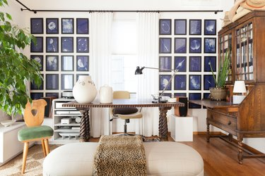 office space with artwork on the walls and wooden desk with wooden dresser nearby