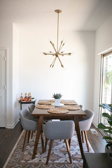 Small dining room storage idea with midcentury chandelier and bar cart