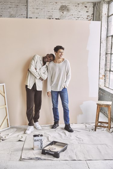 two figures in front of a partially painted wall