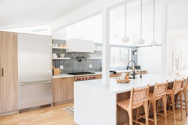 modern kitchen island with white waterfall countertop and wood cabinets