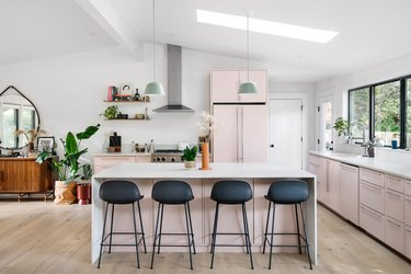 modern kitchen island in pink and white space with black stools