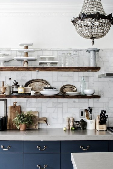 marble subway tile kitchen backsplash with open shelving and blue cabinets