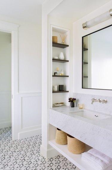 bathroom storage idea with built-in niches and towel storage under sink