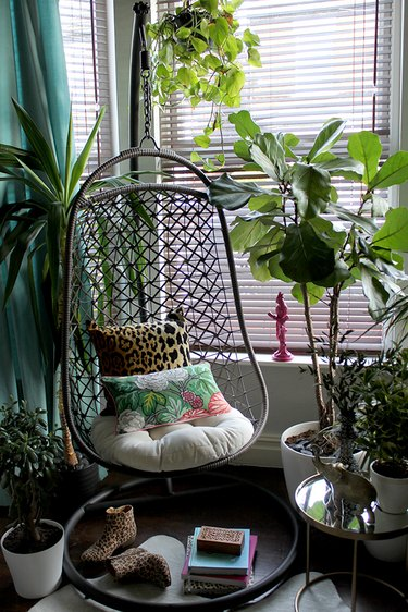 tropical living room with hanging chair and animal print throw pillow